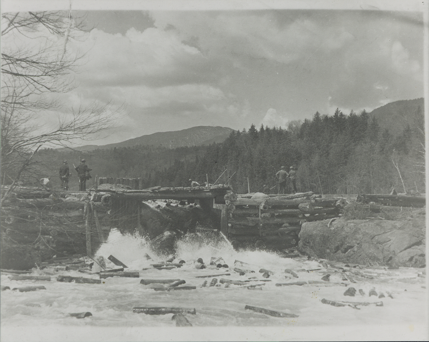 Loggers move logs through a dam gate on Henderson Lake, NY in 1935.