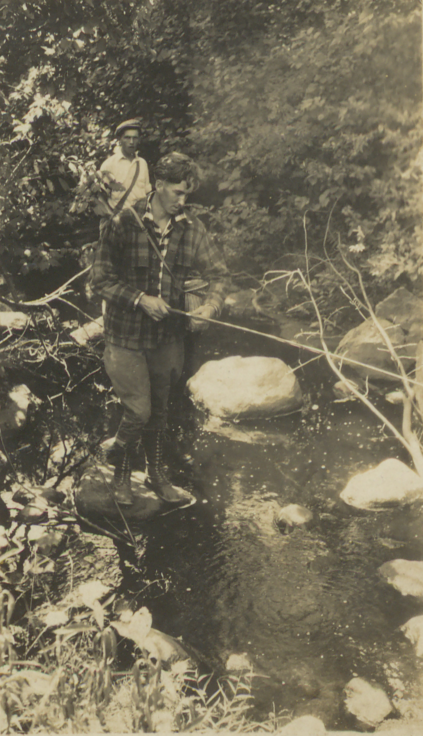 Paul Schaefer and an unidentified man, possibly his brother Vincent, fishing in a stream, circa 1930. Paul stands on a rock in the stream holding a fishing rod and a fishing basket wearing a plaid hunting jacket.  The unidentified man is standing behind him wearing a white shirt and a newsboy hat.