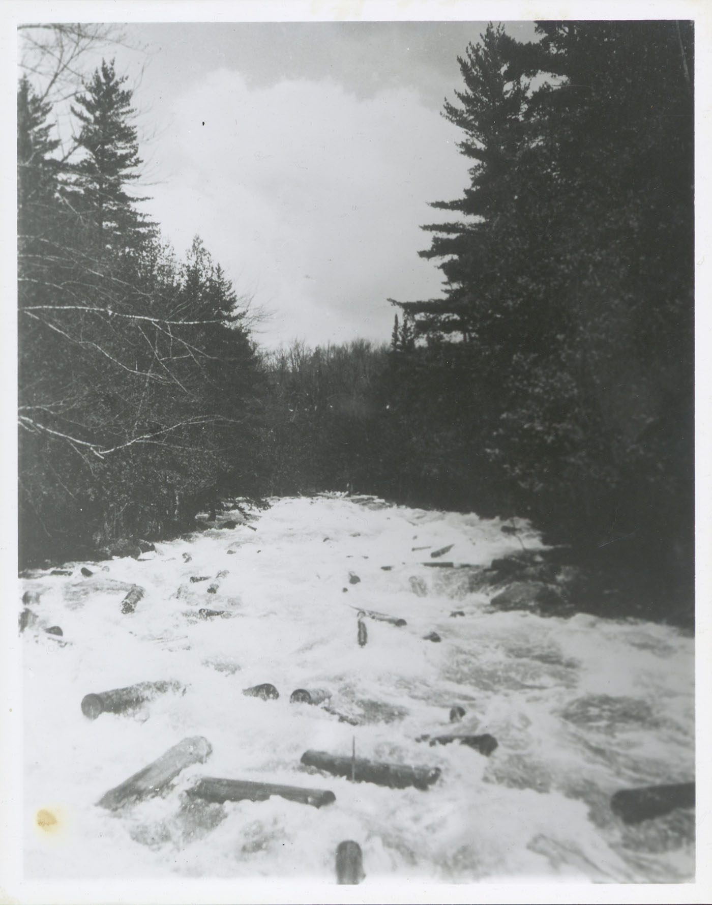 Hundreds of loose logs float down Henderson River damaging the shore line, May 1931. Bill Gluesing and Paul Schaefer took this on a trip to photograph Indian Pass from Henderson Lake.