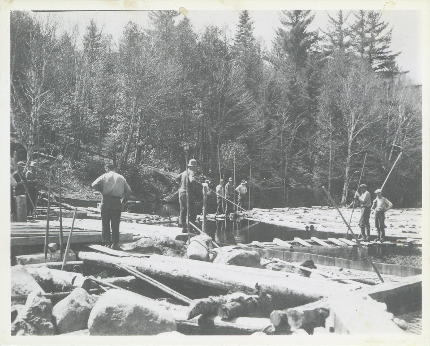 River drivers standing on docks on Henderson Lake, NY surrounded by logs, May 1931.  They are waiting for the wind to change from the south to the west to blow the logs across the lake to a dam which will send them down the Henderson River to the lumber mills on the Hudson River.  Bill Gluesing and Paul Schaefer took this on a trip to photograph Indian Pass from Henderson Lake.