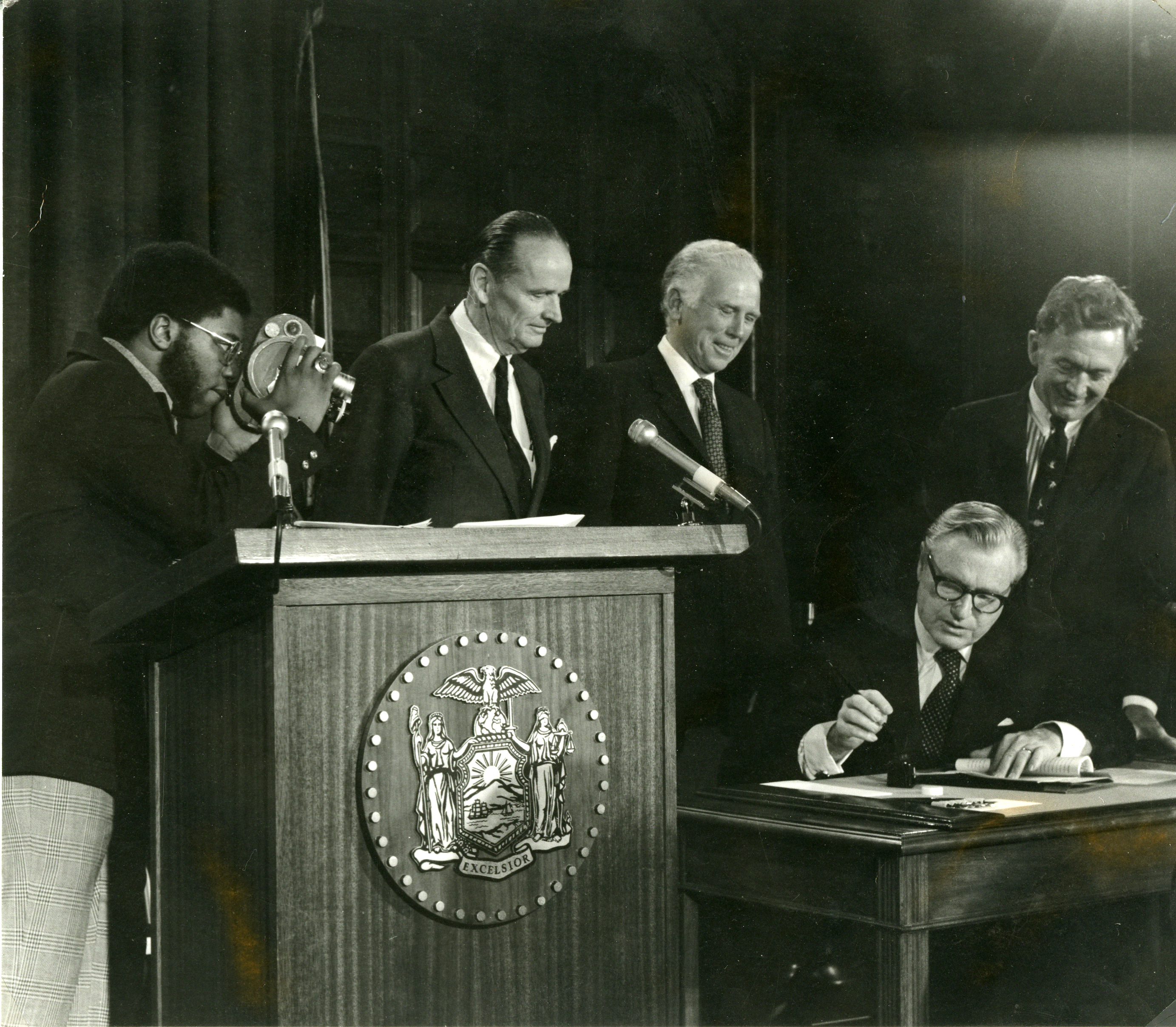Governor Nelson Rockefeller signs the Adirondack Park Agency's Private Land Use and Development Plan into law in 1973. Behind him stand APA Chairman Richard W. Lawerence (left), Perry Duryea (center) and Bernard C. Smith (Right), Chairman of the New York State Senate's Environmental Conservation Committee.