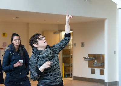 Artist Georgie Friedman pointing to her video installation