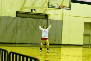 Brianna Duran serves the ball over the net.