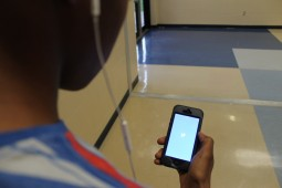 Johnson student opens up the Twitter app in the hall