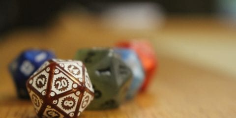 4 20 sided dice sit on a wooden shelf