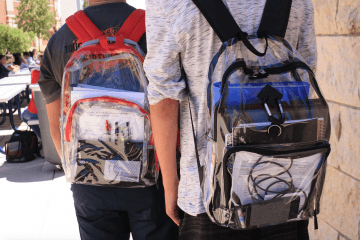 Two students walking outdoors with their clear backpacks.