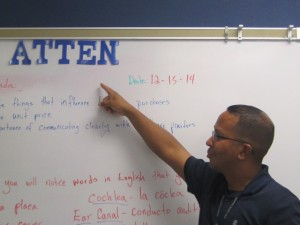 Mr. Bridges is pointing at the word and it seems that his second period class only needs a couple of letters to complete the word.