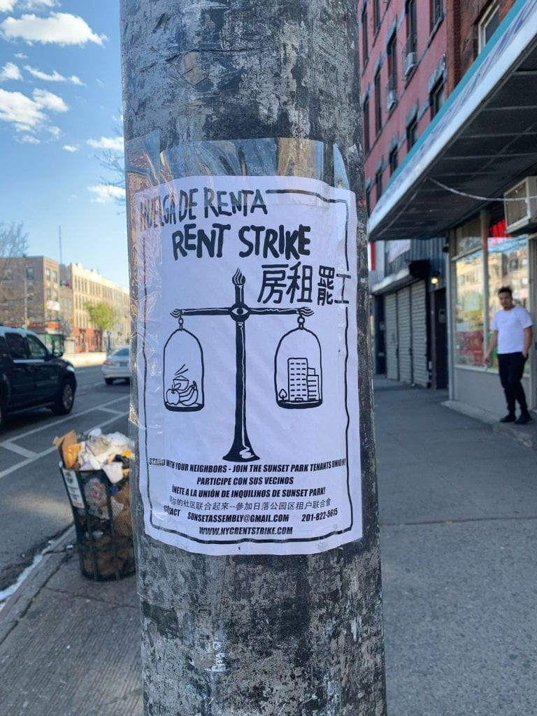 This is a picture of a sign post that says 'Rent Strike' in English, Spanish, and Chinese -- taken in Sunset Park, NYC.