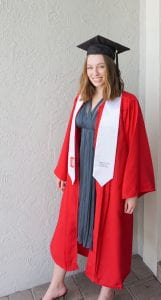 A young woman with light brown wavy hair, fair skin, and blue eyes smiles at the camera, which is in front and slightly to the left of her. She wears a black graduation cap and tassel, red pleated graduation robe, and white stole over a blue/grey long, flowy, V-neck dress.