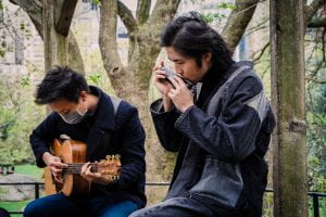 Two AAPI musicians are performing at Central Park, one playing the harmonica and the other playing the guitar.