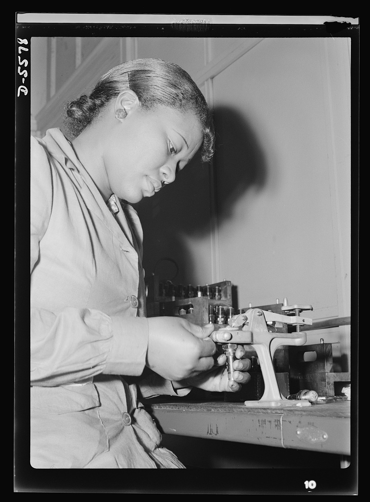 United States Office Of War Information, photographer by Rosener, Ann. Production. Aircraft engines. Reconditioning used spark plugs for reuse in testing airplane motors, Mighnon Gunn operates this small testing machine with speed and precision although she was new to the job two months ago. A former domestic worker, this young woman is now a willing and efficient war worker, one of many women who are relieving labor shortages in war industries throughout the country. Melrose Park, Buick plant. July, 1942. Image. Retrieved from the Library of Congress, .