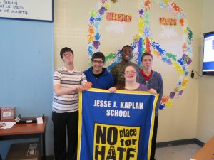 Image of Kaplan students posing with the No Place for Hate banner