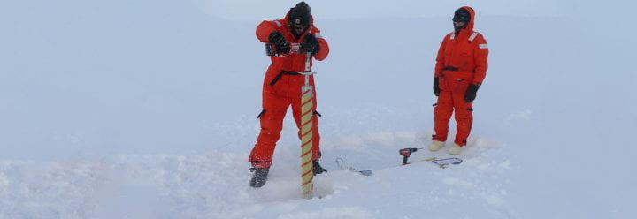 Kyle Dilliplaine drills an ice core at the North Pole ice sampling station as UC Santa Cruz ocean scientist Carl Lamborg looks on, photo credit Bill Schmoker PolarTREC 2015 courtesy of ARCUS-