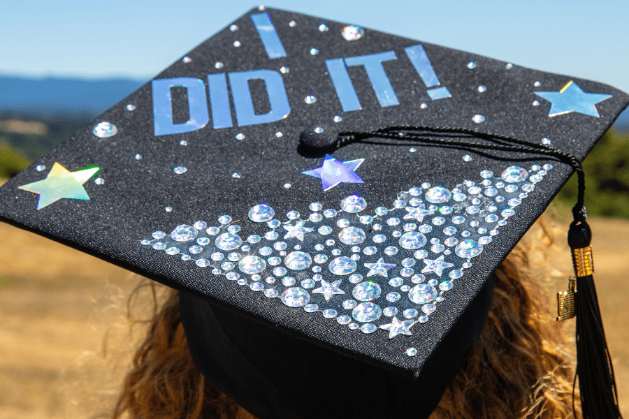 """A woman wears a graduation cap that reads """"I did it"""" in bold blue lettering, surrounded by glitter and stars."""
