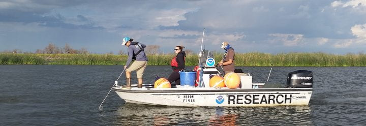"""Three people standing on a small boat that has the word """"research"""" printed on the side."""