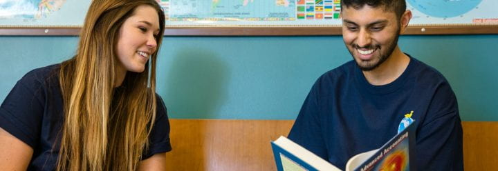 Two students seated in front of a map of the world, reading an accounting textbook