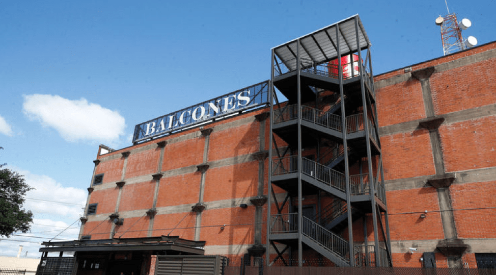 Image of Balcones Distillery. It is a brick building with a metal fire escape. The name appears on the roof in large white lettering.