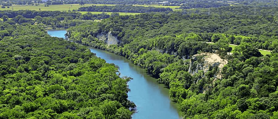 Aerial image of the Brazos River going through Cameron Park. The banks of the river are thick with green tree canopies and two rock faces.