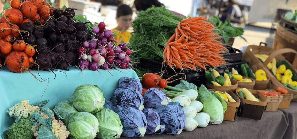 Image of brightly colored vegetables lined up on a table at the Waco Downtown Farmers' Market