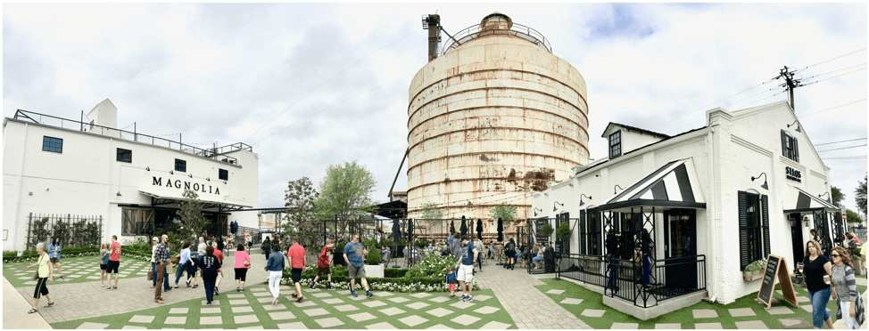 Image of Magnolia Market in Waco, TX. A silo appears in the background, with two white buildings in the foreground: the bakery and market. People are milling about the manicured lawn