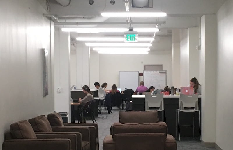 A view into the new study space with cushioned chairs in the foreground and students at worktables in the background.