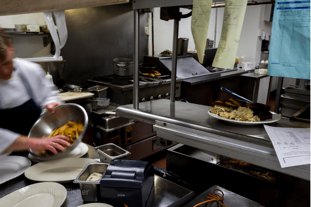 Photo of a busy restaurant kitchen, with a blurred worker in the foreground mixing food in a bowl