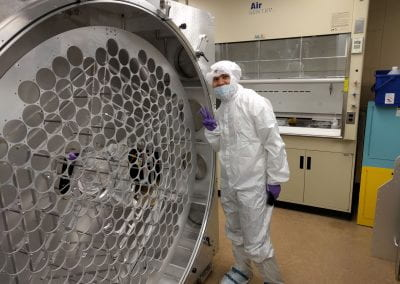 Samuel Chan posing in the Brown cleanroom with an empty PALACE enclosure