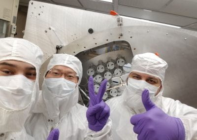 Several Brown workers in the cleanroom, gesturing positively towards the camera