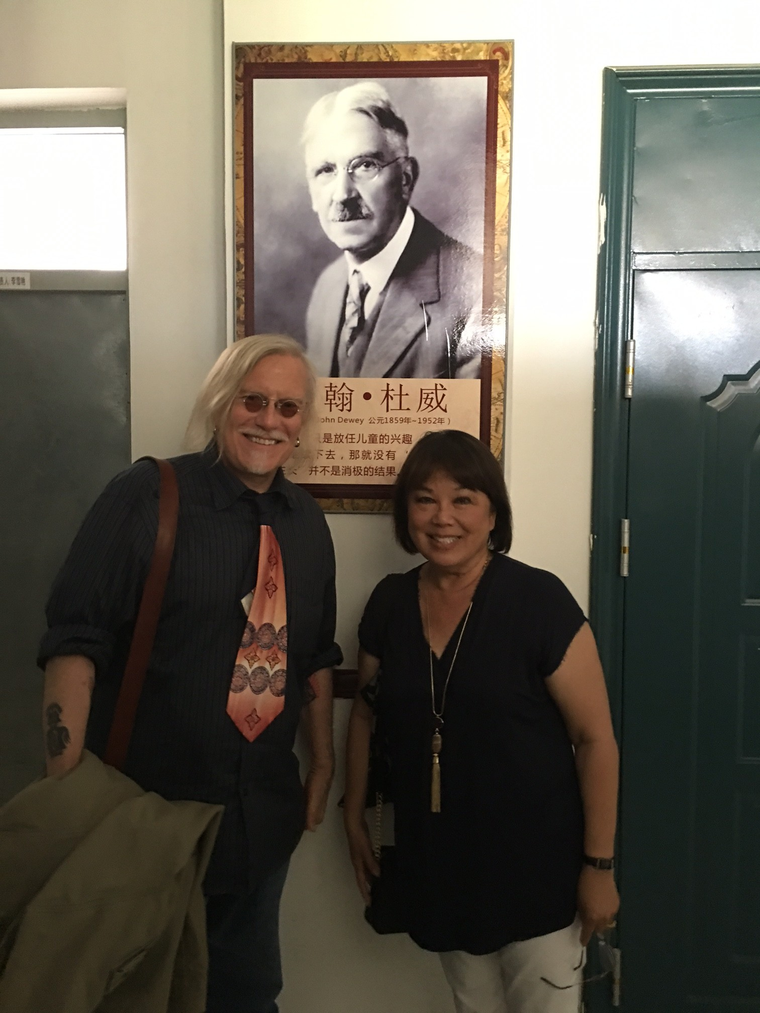 Peter and  Suzi in Siping, with image of John Dewey