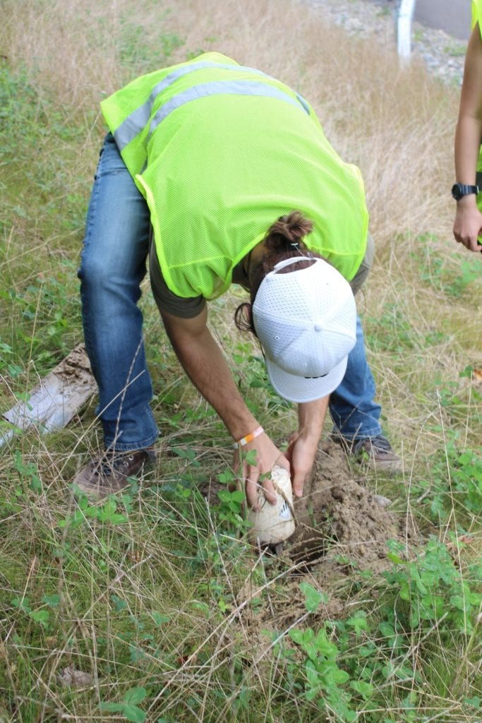 A student volunteer places a seismic node into the ground.