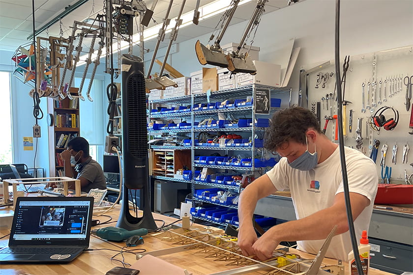 A photgraph of two students working in a robotics lab.
