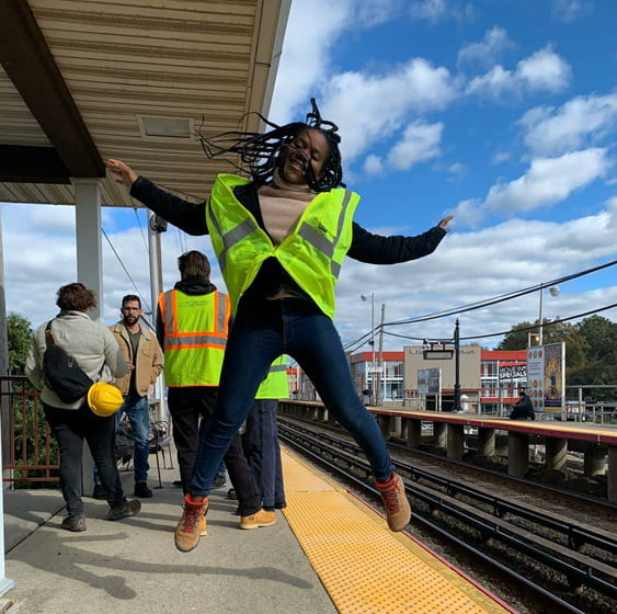 Photograph of a student jumping in midair by a subway stop.