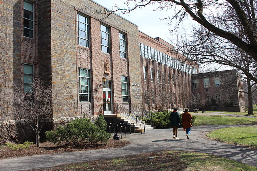 A photograph of two students walking in front of Olin Hall