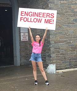 Cornell Engineering peer advisor holding a sign that says,