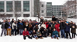 Group photo of students with their professor after having a snowball fight in physics class.
