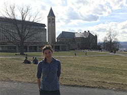 A photograph of Cornell Engineering student Sydney standing on the Arts Quad with the Clock Tower in the background