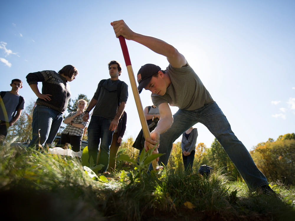 A photograph of students burying a seismograph
