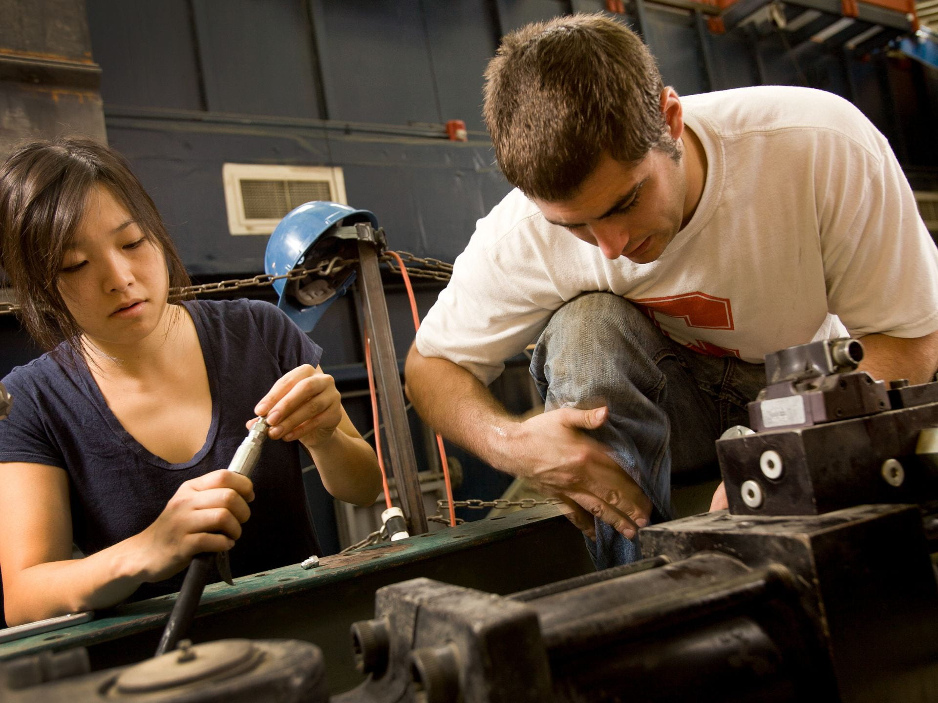 A photograph of two students working on a car engine