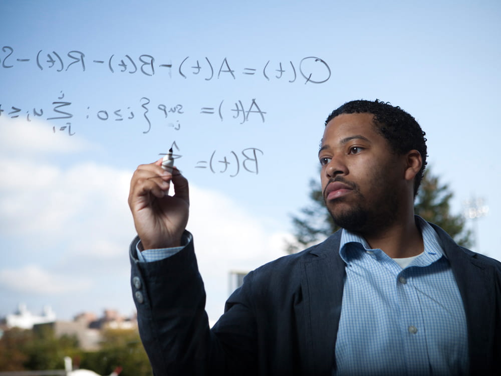 A photograph of a student writing an equation.