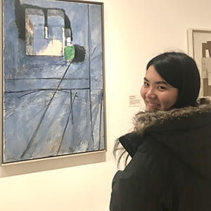 A photograph of Cornell ENgineering student Reina in front of a painting