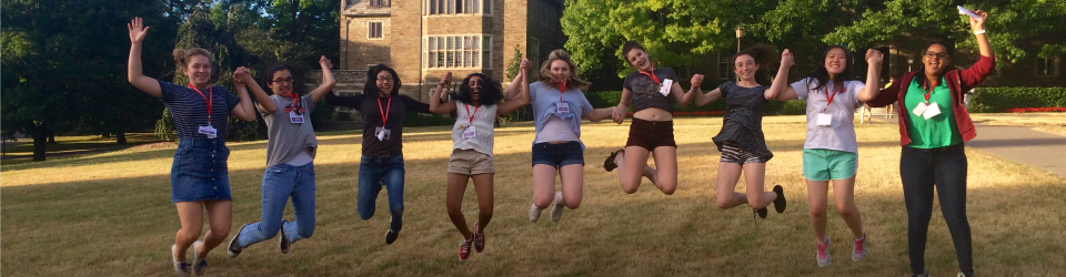 Students with arms linked jump in the air