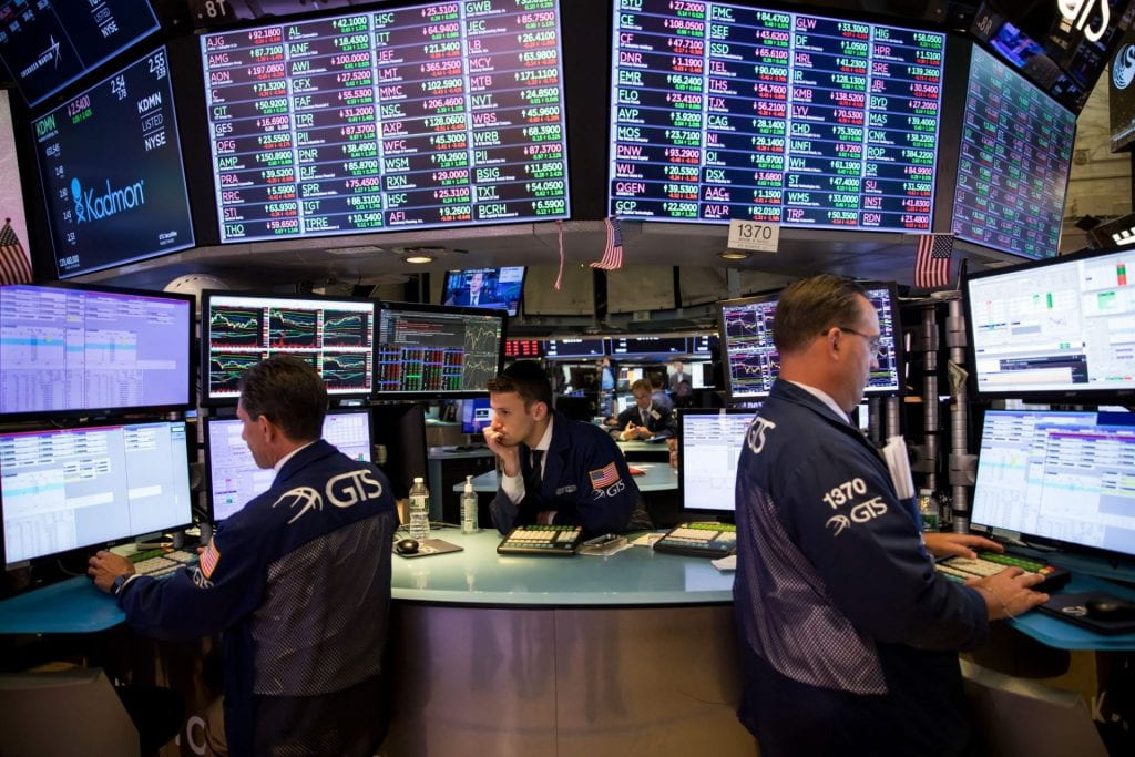 Three male stock traders at computers