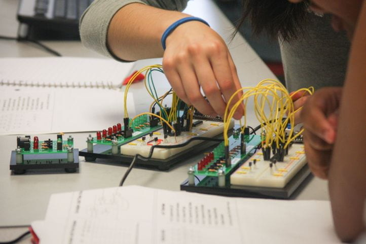 Hand hovering over a custom-made LED/switch board; hardware to be used on 2021 CURIE project