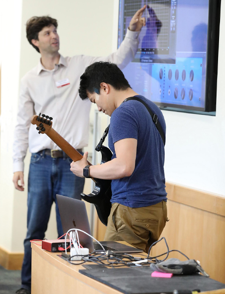 A student demonstrates vibrations using an electric guitar. The readings are projected on a screen in the classroom.