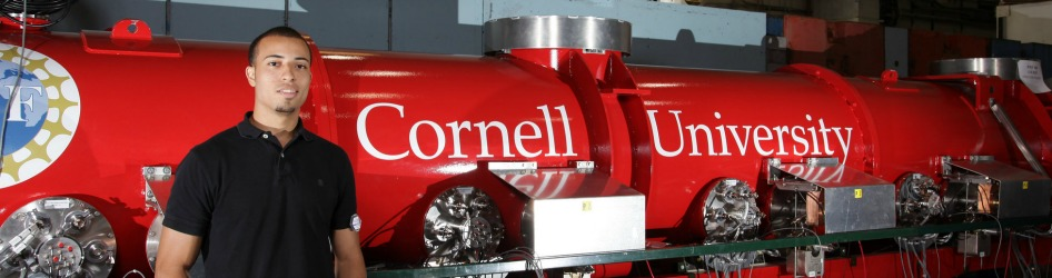Male researcher posing in front of red Cornell logo