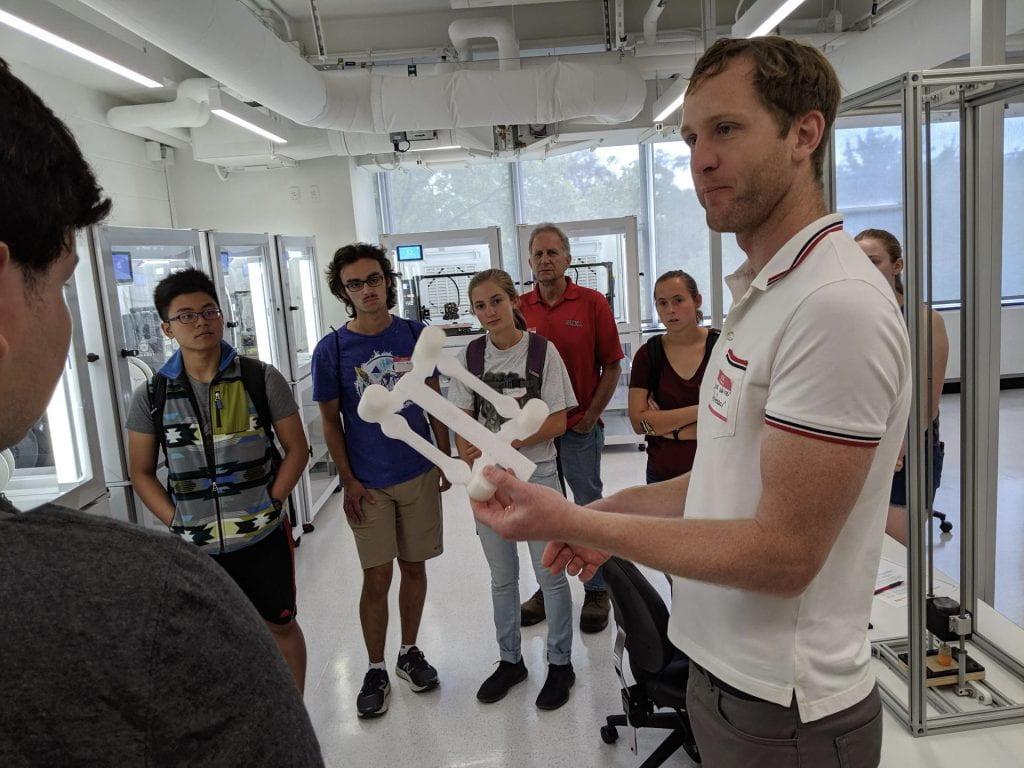 Derek Warner holding up a 3D model of an airplane part.