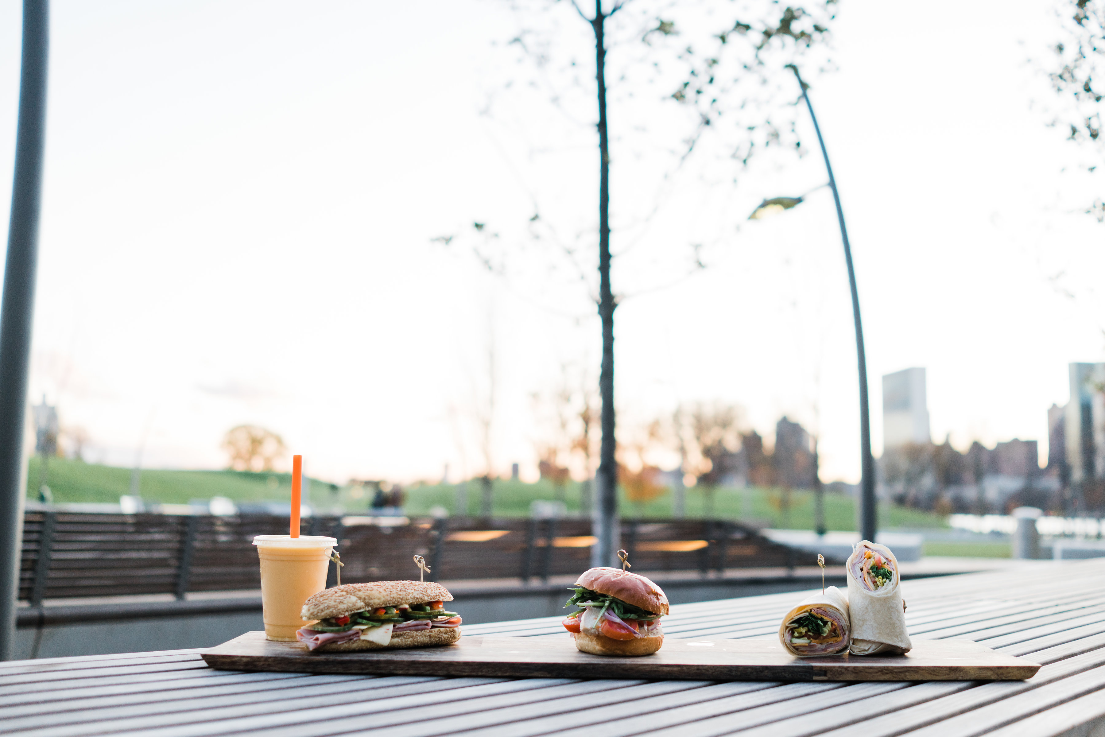 table in a park with food items ontop: a drink in a plastic cup and straw with a sub-sandwich, a large burger, and a wrap sandwich sliced in two