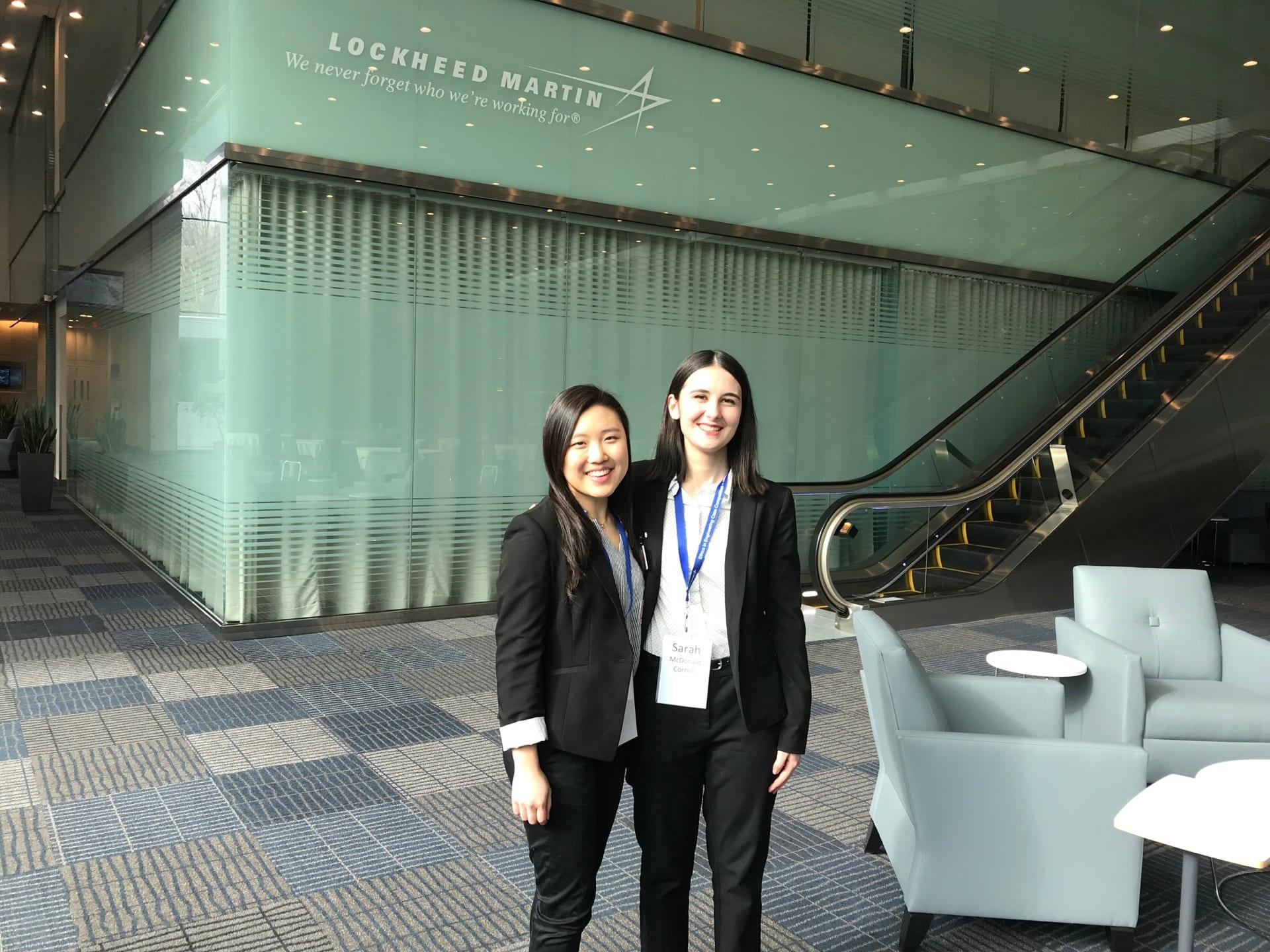 Sarah MacDonald and Adeline Tse stand beneath a Lockheed Martin Co. sign