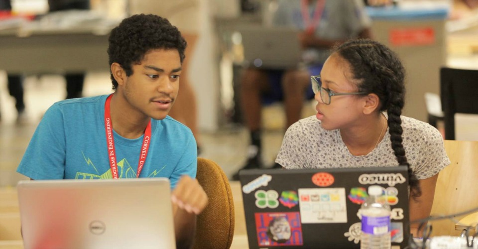 Male and female participant discuss project behind their laptops
