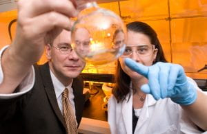A male faculty member in a business suit is in a chemistry lab and holding a clear glass Florence flask containing a clear liquid. A female student wearing goggles, a white lab coat, and blue disposable gloves is pointing to the contents of the flask.